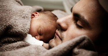 baby and father under brown blanket