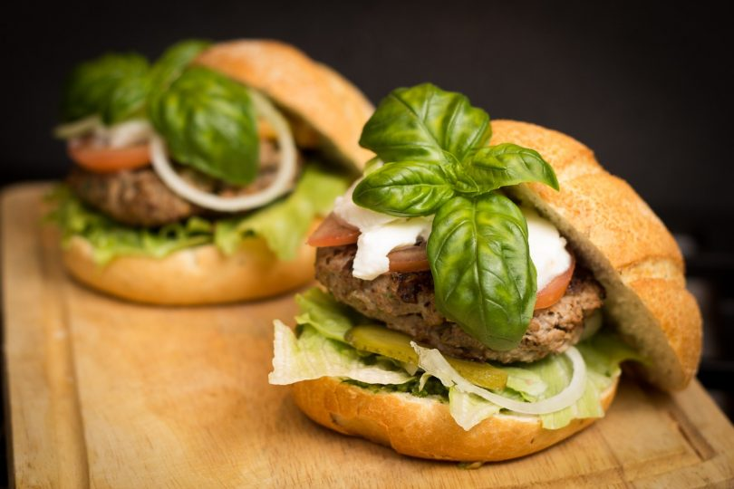 two hamburgers with basil on top