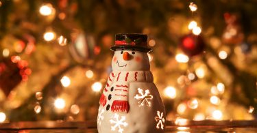 christmas tree with lights and snow man in front of it