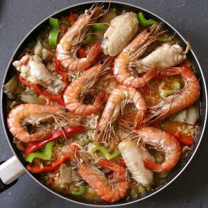 seafood paella with shrimp on top