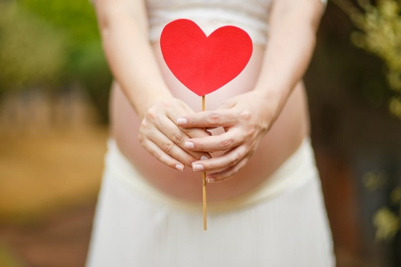 pregnant woman with red heart in front of her