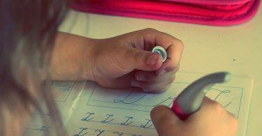 child learns to write letter Z