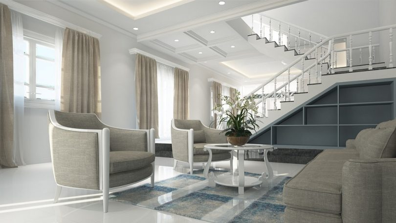 living room with light coloured furniture and white stairs