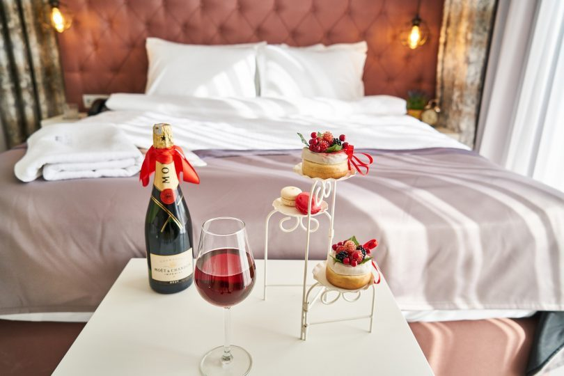romantic hotel room with champagne and little cakes