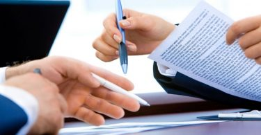 two people with contract and pen