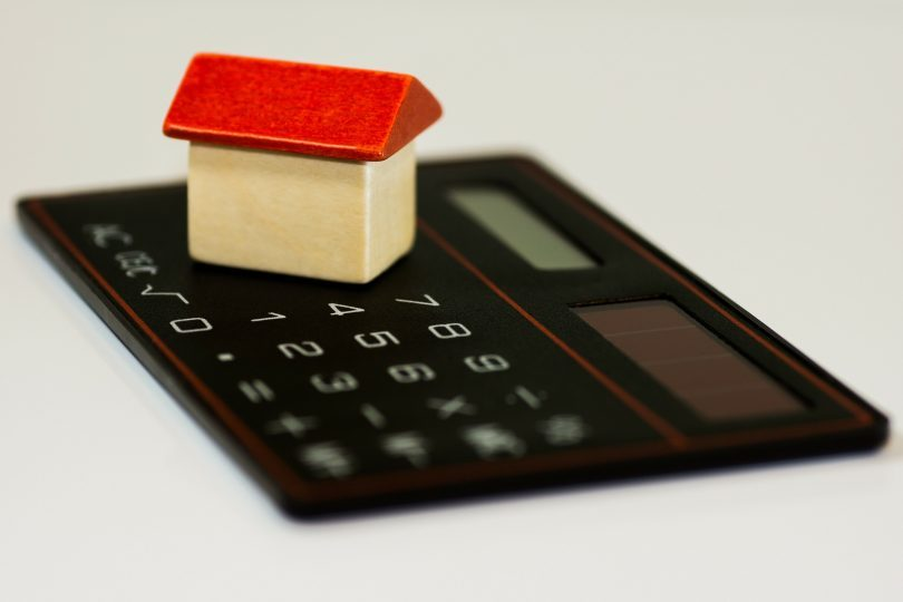 calculator with small white house and red roof