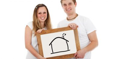 young couple holding drawing of a house
