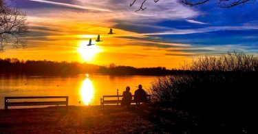two people on bench watching sunset over water