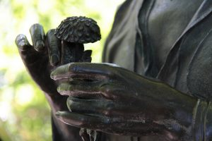 bronze art of person holding flower