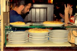 lots of plates on the bar,, 3 with tortillas on top