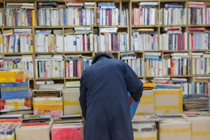 busy interior bookstore with man bending over to check book