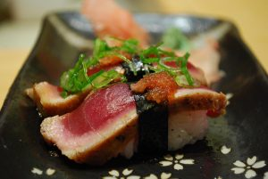sushi with tuna on top on black plate