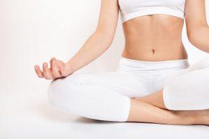 female in white meditating