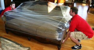 moving company transports couch in plastic wrapping