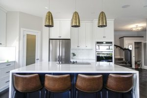 white kitchen with brass lamps and leather chairs