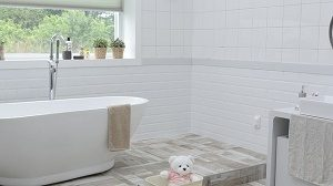 white bathroom with bath tub and window
