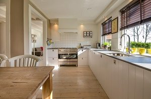 white kitchen with windows and wooden table