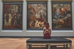 lady sitting on bench in front of paintings