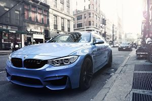 light blue bmw in big city