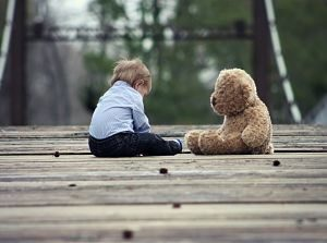 child and bear sitting on floor
