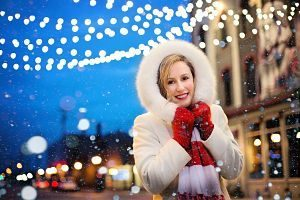 lady in white coat and red gloves with christmas lights in background