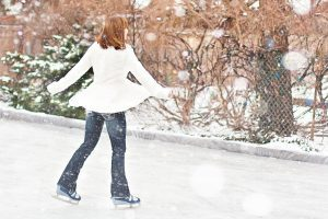 lady in white jacket ice skating outside