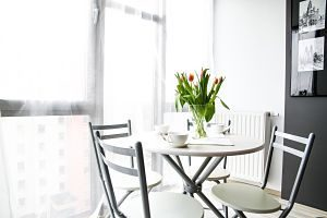 white table with white chairs and tulips